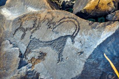 Close up of ancient pictograms engraved on rock on Saimaluu Tash site in Kyrgyzstan